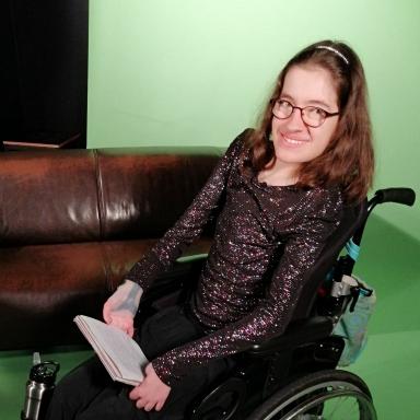 Laura sitzt im Rollstuhl vor einem Sofa. Grüner hintergrund. in den Händen hält sie Karteikarten