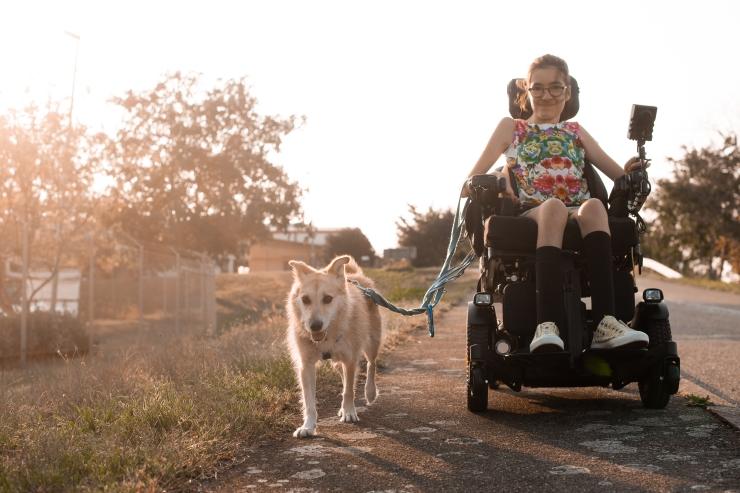 Laura fährt im Elektrorollstuhl im Sonnenuntergang. Sie hat einen Hund an der Leine.
