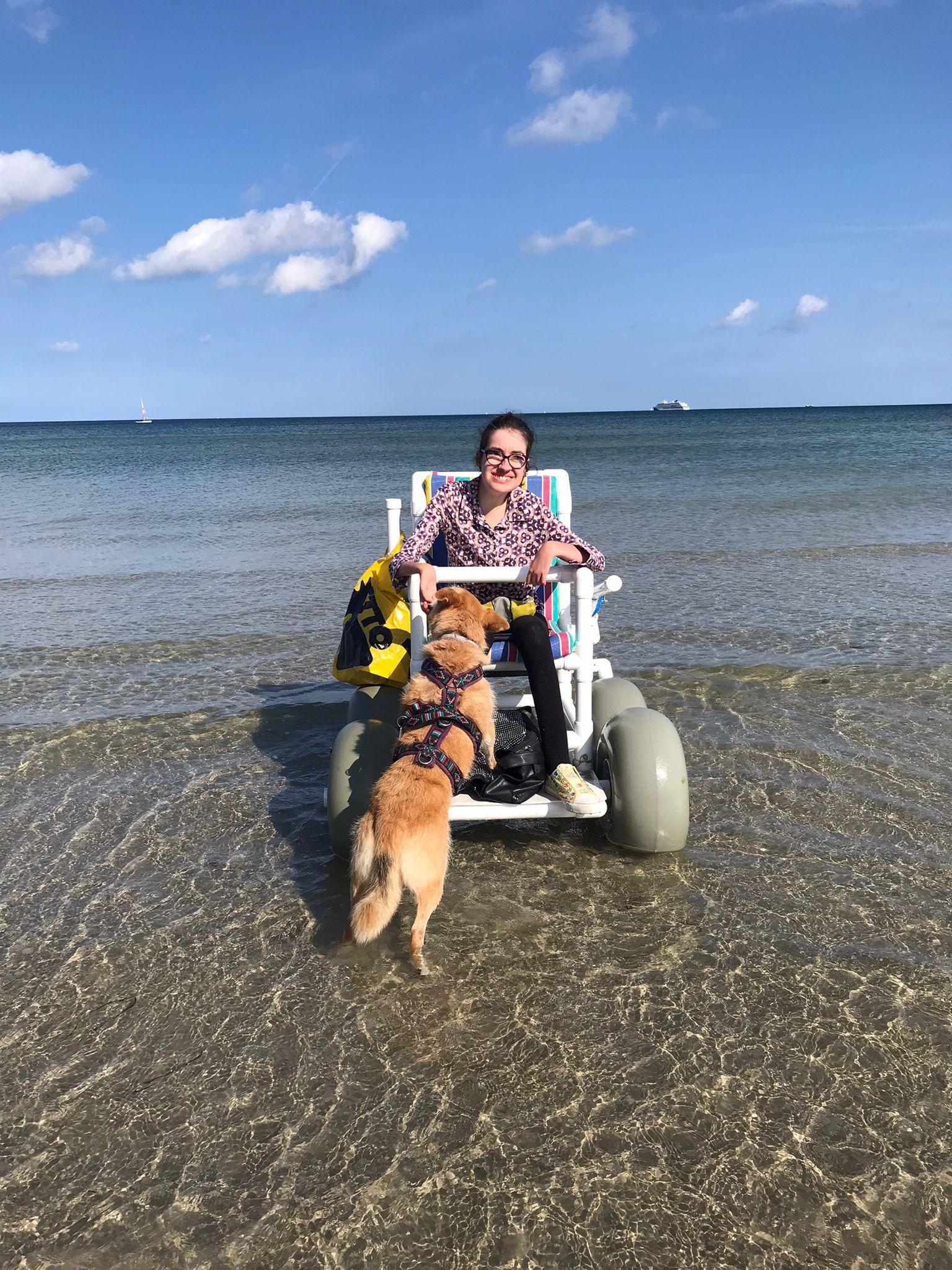Laura ist mit dem Strandrollstuhl im Wasser. Ein Hund steht mit dem Rücken zur Kamera und steht mit den Vorderfüßen auf dem Fußtritt des Rollstuhls um weniger Wasser zu sein.