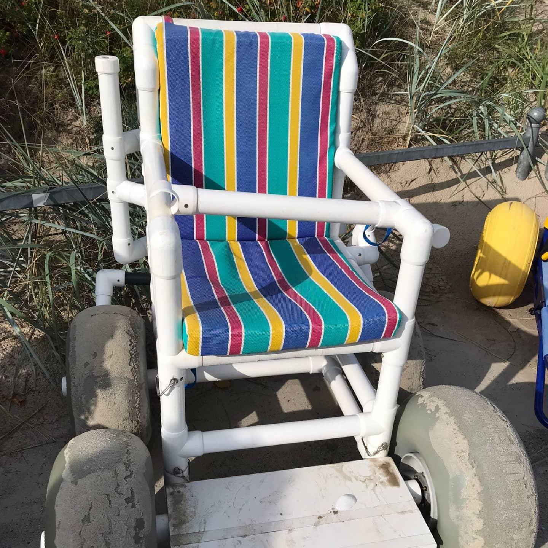 Auf dem Foto sieht man einen Strandrollstuhl. Es ist ein Gefährt, mit besonders breiten Rädern. Das Fahrgestell besteht aus Röhren und das Sitzpolster ist bunt gestreift.